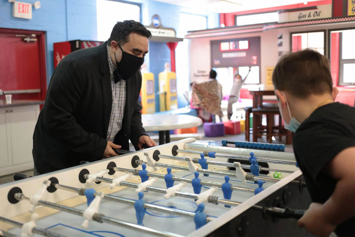 Juan Perez, senior director of program excellence at Boys & Girls Clubs of Western Pennsylvania's Carnegie clubhouse, plays foosball with 8-year-old Dennis Moehring on March 3. (Photo by Ryan Loew/PublicSource)