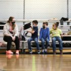 Amber York (left), a youth development professional with Boys & Girls Clubs of Western Pennsylvania serving through AmeriCorps, sits with students during a gym period at the organization's Lawrenceville location. (Photo by Ryan Loew/PublicSource)