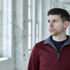 Josh Gyory, a 28-year-old Ph.D. candidate at Carnegie Mellon University, is pictured in a red sweater against a light background. He has short dark hair and light stubble.