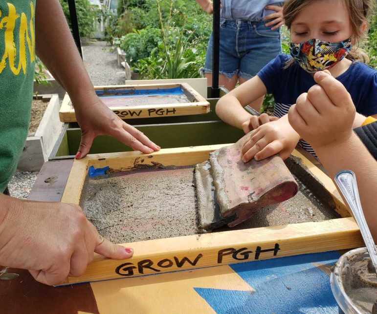 Violet Gabriel does screen printing with mud at the Etna community garden. Etna was the first local garden to check out Mary Tremonte's educational cart. (Courtesy photo)