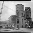 Historic photo of Bethel AME Church, a large, Romanesque-style cathedral, amid demolition. A crane hovers over the building, and a few construction workers stand in front.