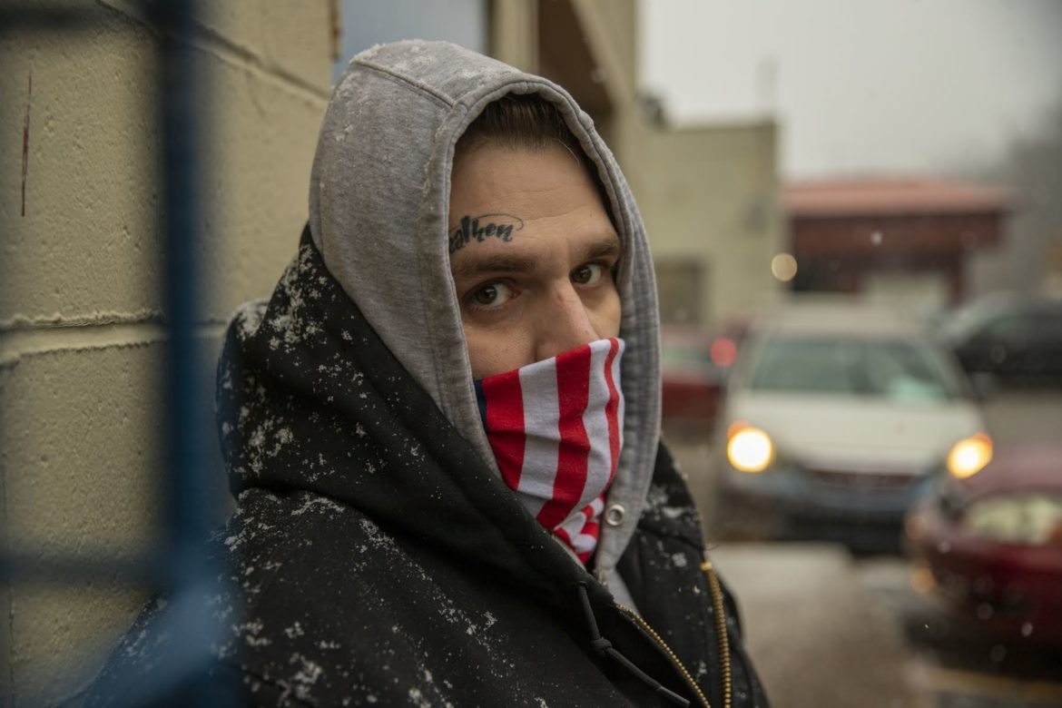 Justin Rape wears a grey hoodie with the hood up, black jacket and American flag face mask. He is standing outside of a building in the snow.