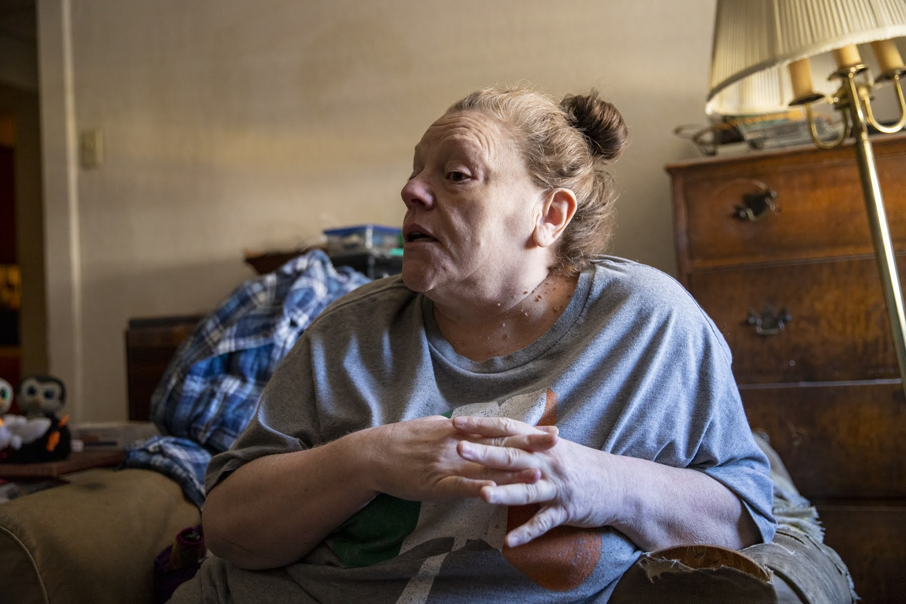 Mary Ellen Barber, 58, sits in the living room of her apartment in Avalon, in which she endured a leaky roof during March rains. (Photo by Jay Manning/PublicSource)
