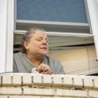 Mary Ellen Barber peers out the window of her second-story apartment in Avalon. She fended off one eviction filing by her landlord, but knows she may imminently face another. (Photo by Jay Manning/PublicSource)