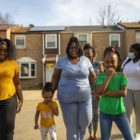 The family of Jasmine Devine (third from left) including daughters (from left) Jah'Niya, Erionna and Nylah, plus Mary Hester (rear) of LifeVenture Real Estate Services, and Brettney Duck (far right) of Catapult Greater Pittsburgh, walk through Enright Court on March 30, 2021. (Photo by Jay Manning/PublicSource)