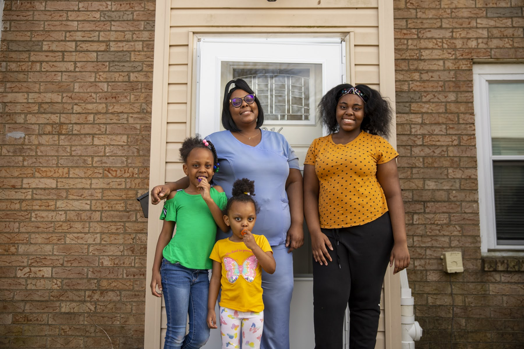 Jasmine Devine (rear) and her three daughters (from left to right) Nylah (6), Erionna (3) and Jah'Niya (13) stand in front of the townhouse they now rent in East Liberty's Enright Court. (Photo by Jay Manning/PublicSource)