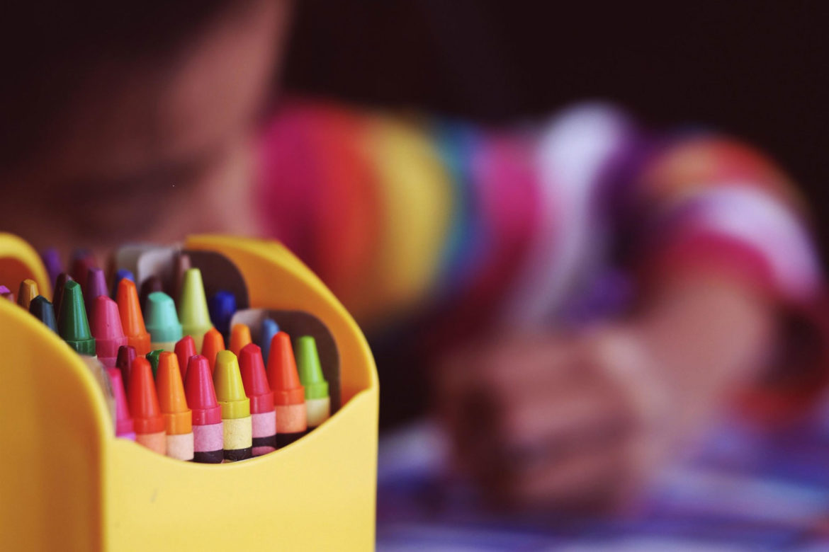 Crayons beside child coloring.