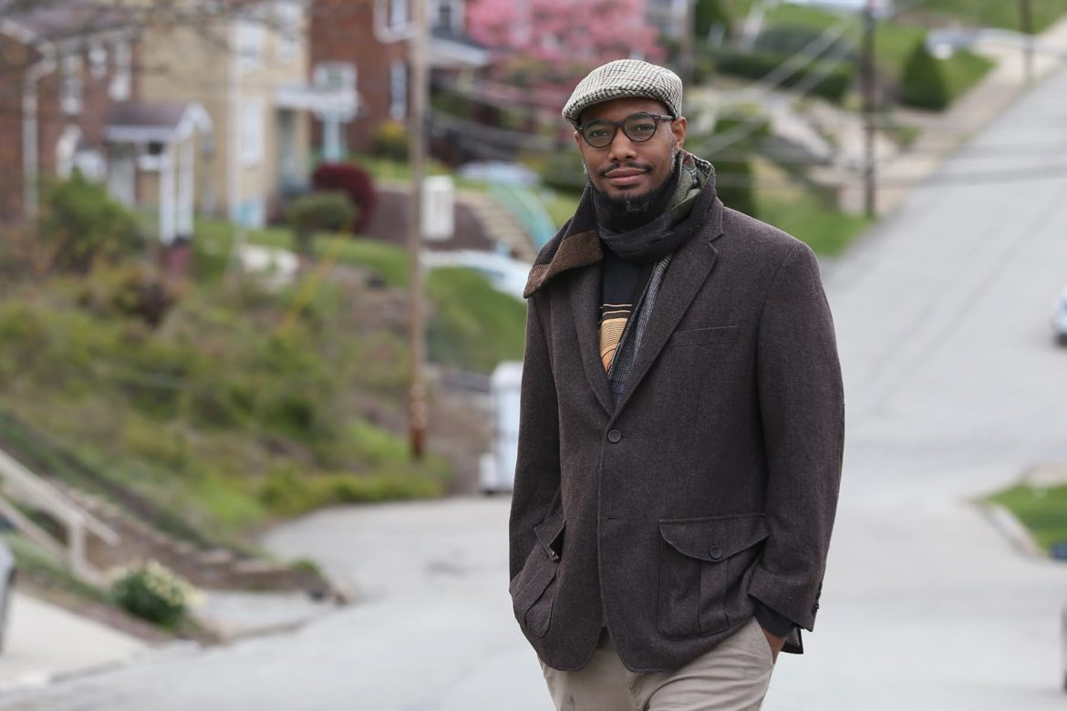 Ali R. Abdullah, a tall African American man with glasses, stands with his hands in his pockets on a street by his home.