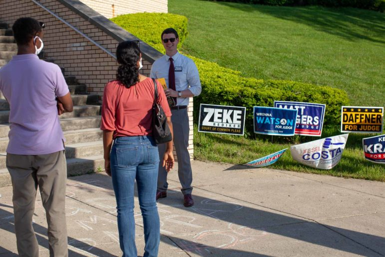 Zeke Rediker, a candidate for the Allegheny County Court of Common Pleas, talks to voters outside of the polling place at Taylor Allderdice High School on Tuesday evening.