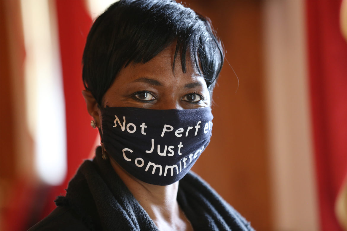"""Rev. Niecy Dennis White wears a face mask that reads """"Not Perfect. Just Committed."""""""