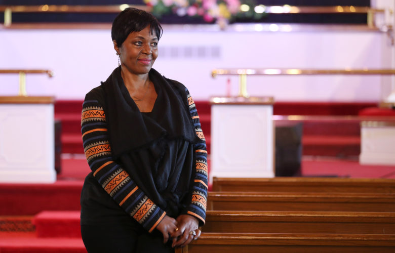 Rev. Niecy Dennis White photographed standing in the pews of The Lord's Church in Monroeville, where she is lead pastor.