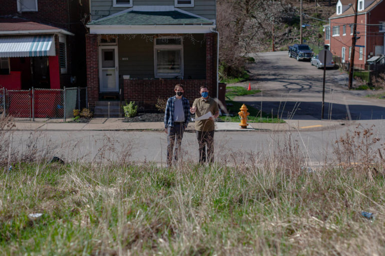 Michael Hiller and Aaron Birdy, the authors of Upstream's equity study, stand in front of Foster-Pinkley's house and the vacant lots where their new rainwater capture project will be built. (Photo by Quinn Glabicki / PublicSource)