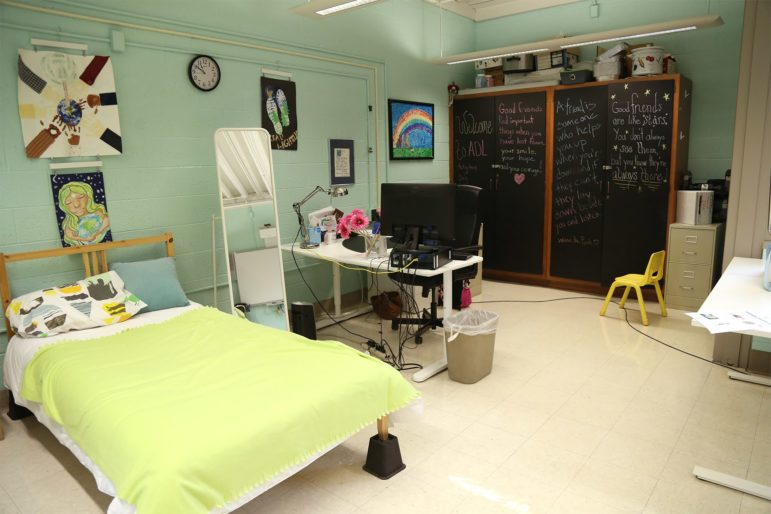 Image shows objects including a bed and mirror in the Activities of Daily Living room at the Pioneer Education Center in Brookline.