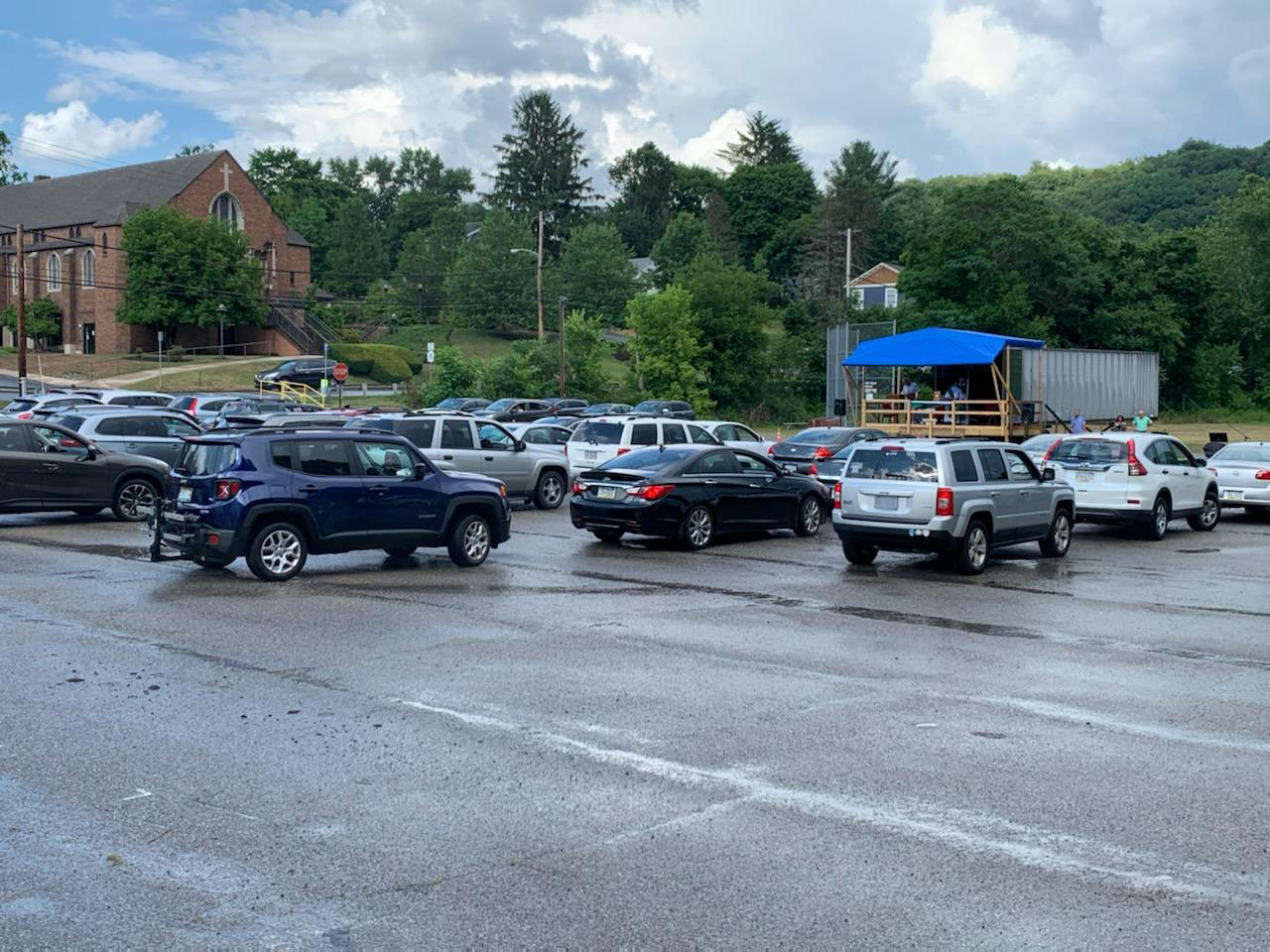 Vehicles gather in the parking lot of St. Ursula Parish as Father Tim Whalen presides over mass from a makeshift platform