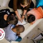 students sitting on a classroom floor doing classwork