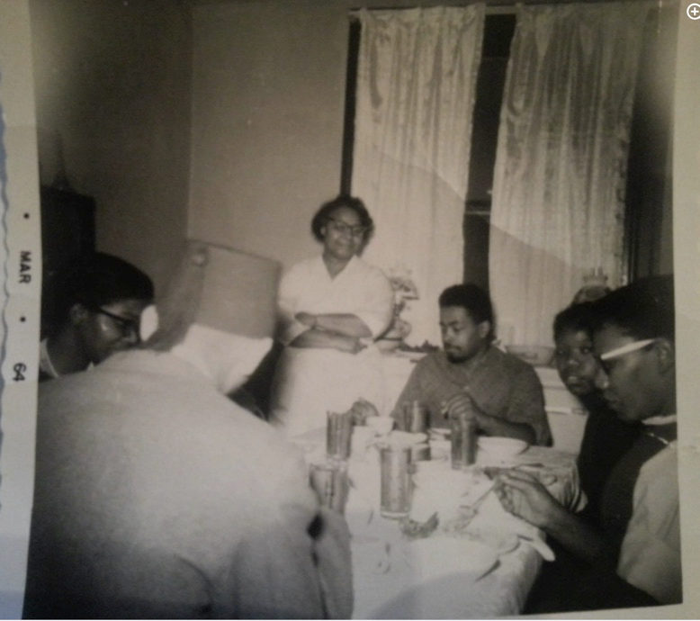 Maneera Deen sits at a table with a small group of young Black Muslim men from her community.