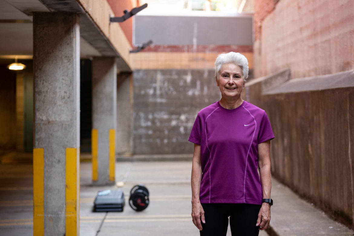Marta Wilkin stands near some exercise equipment while looking into the camera for a photo.