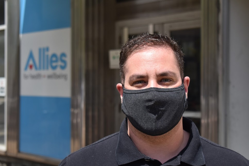 Conrad Kalcich wears a black shirt and a black mask and stands in front of his office in Easy Liberty.