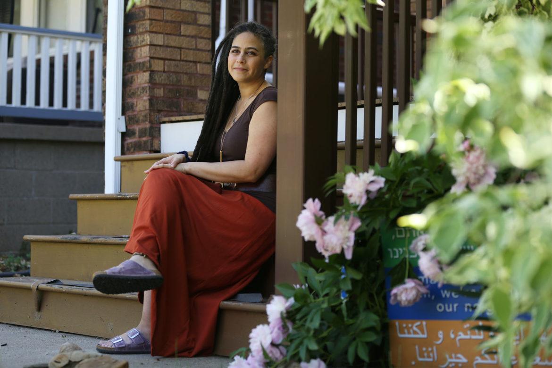 Keshira haLev Fife sits on a porch stair.