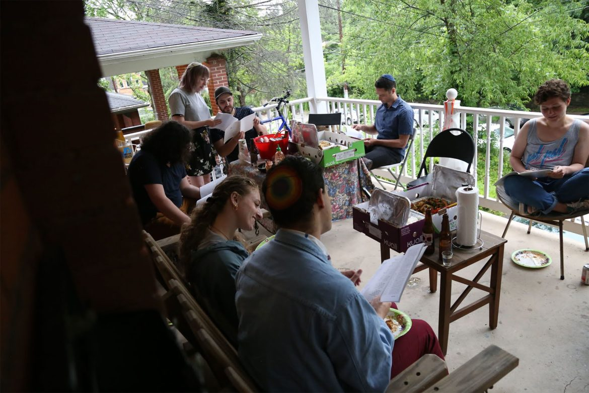 7 guests and residents of Moishe House gather for Shabbat on the Moishe House porch.