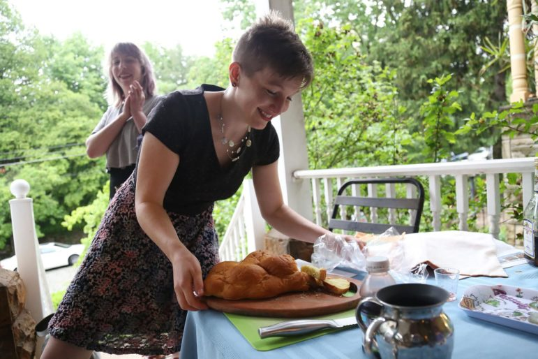 Kayla Reiman picks up a tray of challah from a table on the Moishe House porch.