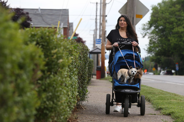 Marisa Haney walks her dogs Sarah and Molly in a stroller down Grand Avenue on Neville Island, where she has lived for 11 years. (Photo by Ryan Loew/PublicSource)