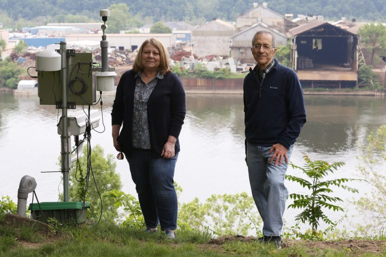 Karen Grzywinski (left) and Angelo Taranto of the group Allegheny County Clean Air Now, stand next to air monitors and a live-streaming camera stationed in Emsworth, across the Ohio River from Metalico, a metal recycling facility on Neville Island. (Photo by Ryan Loew/PublicSource)