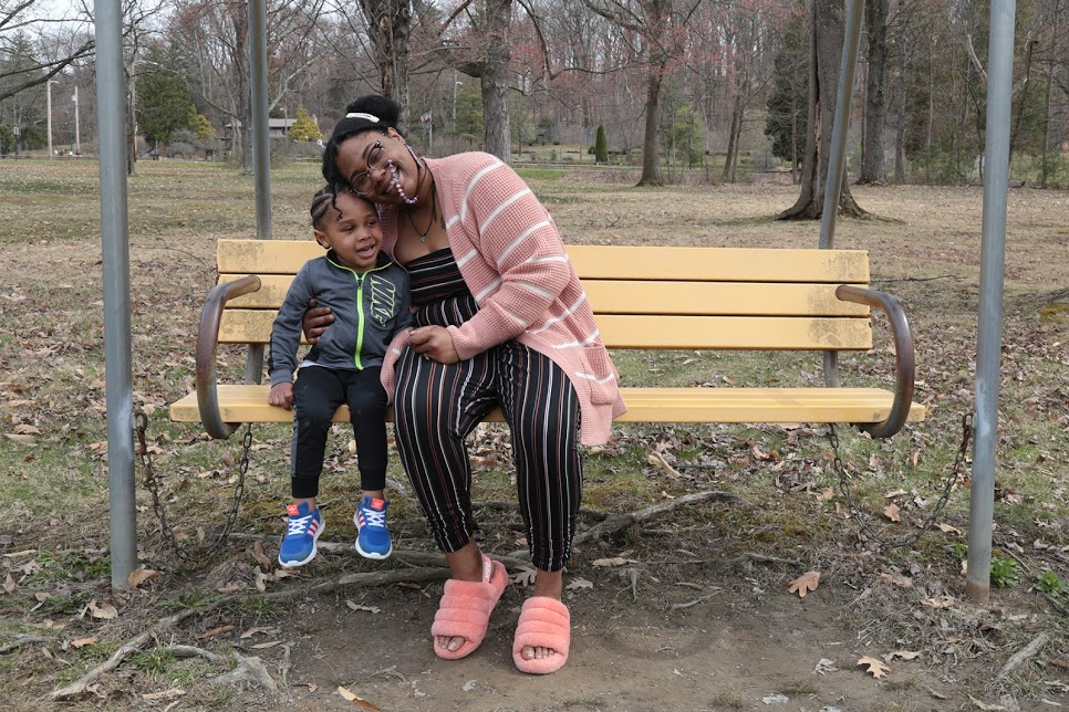 Nina Riley sits on a park bench with her son.