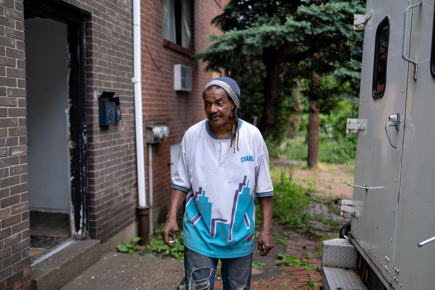 Leslie Burden, a Park Hill Drive resident, photographed outside of his home on May 28, 2021, with an abandoned and decaying unit behind him and a truck that hasn't moved in months. (Photo by Quinn Glabicki/PublicSource)