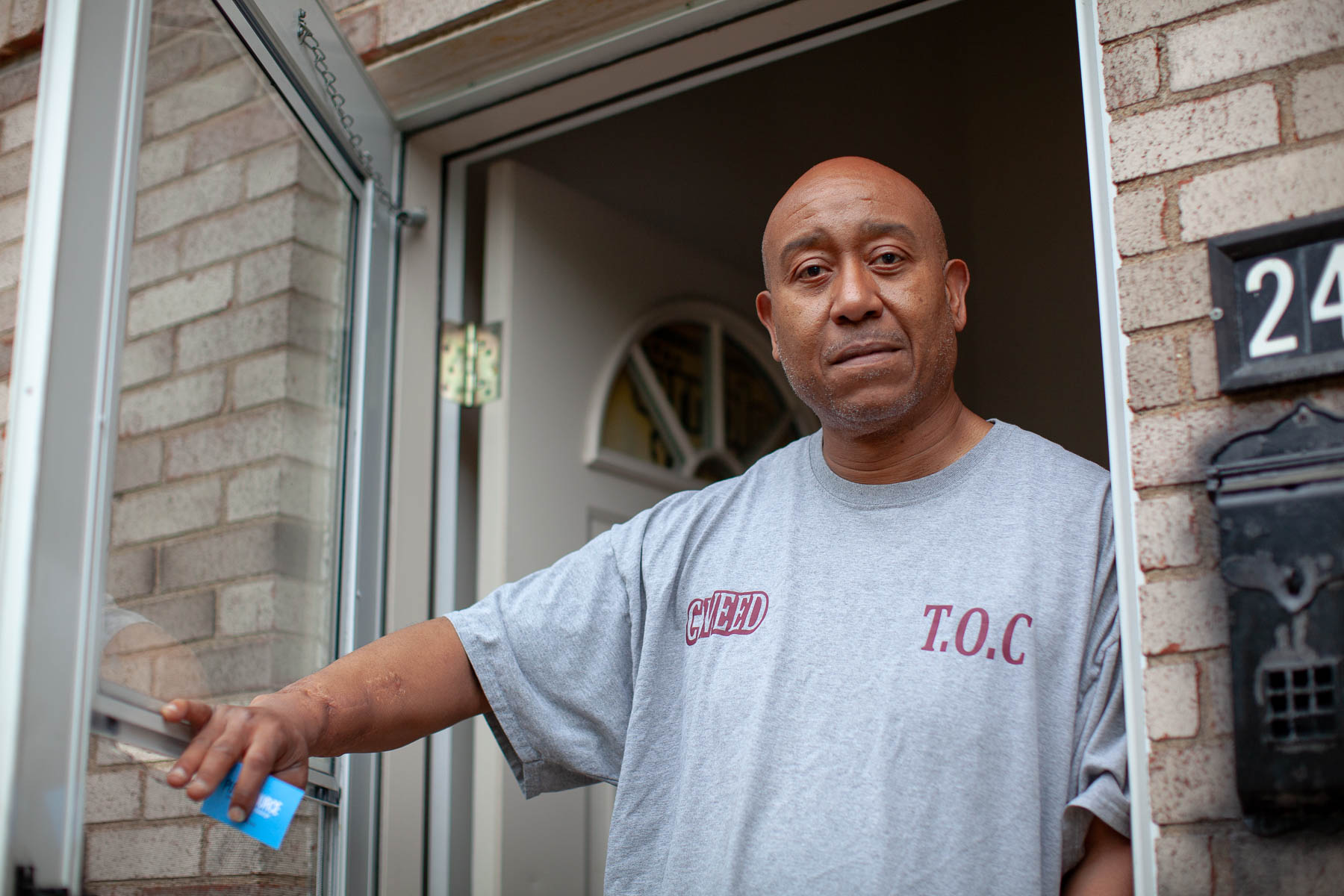 """Chris Thomas is in the process of buying the townhouse he now rents on Park Hill Drive in East Hills. A recent sewage backup created """"a mess,"""" but he loves watching the birds from the front porch. (Photo by Quinn Glabicki/PublicSource)"""