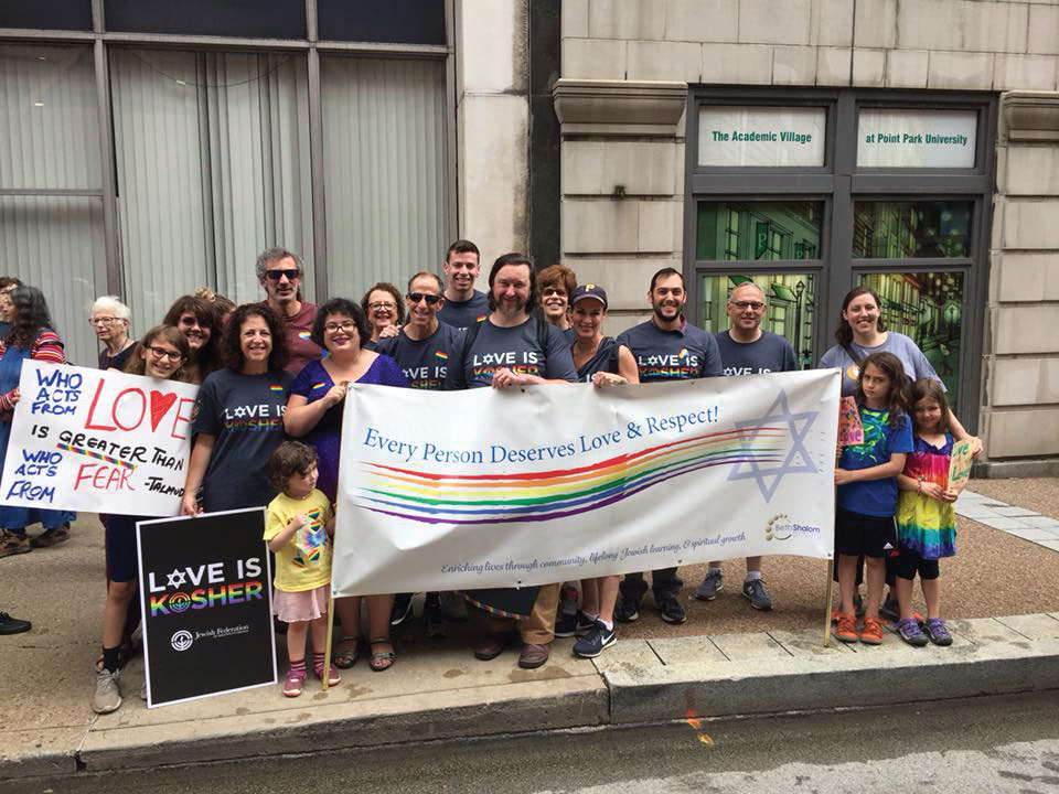 """Members from Congregation Beth Shalom gather outside with a sign that reads """"Every person deserves love and respect"""" and shows a rainbow and the Star of David."""