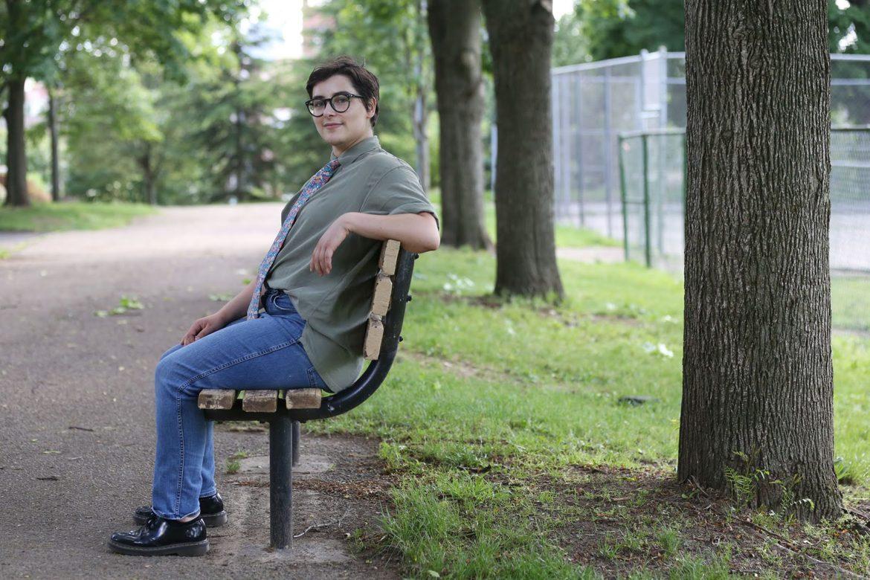 Sai Koros sits on a park bench.
