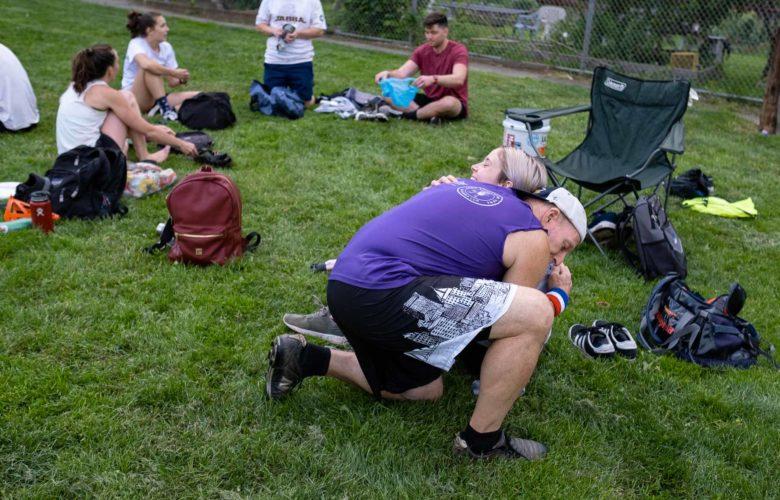 Matt Weiss kneels on a grassy field and hugs another person.