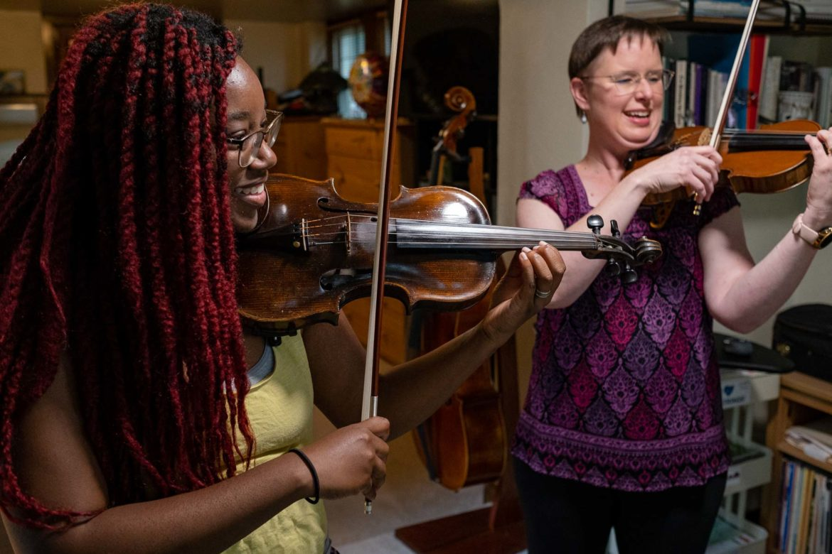 Falencia Jean-Francois holds a violin and its bow near her instructor, who is also holding a violin and bow.