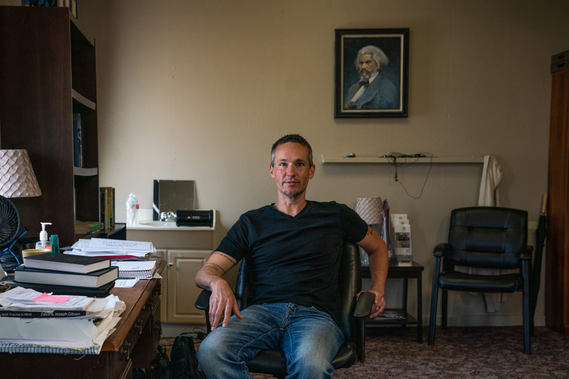 Rev. Nate Keisel in his office at Mosaic Community Church. A portrait of Frederick Douglass hangs on the wall behind him.