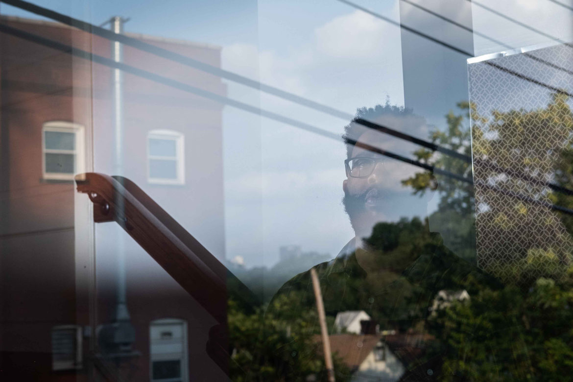 Rev. Justin Louis Murrell photographed through a window at New Culture Church