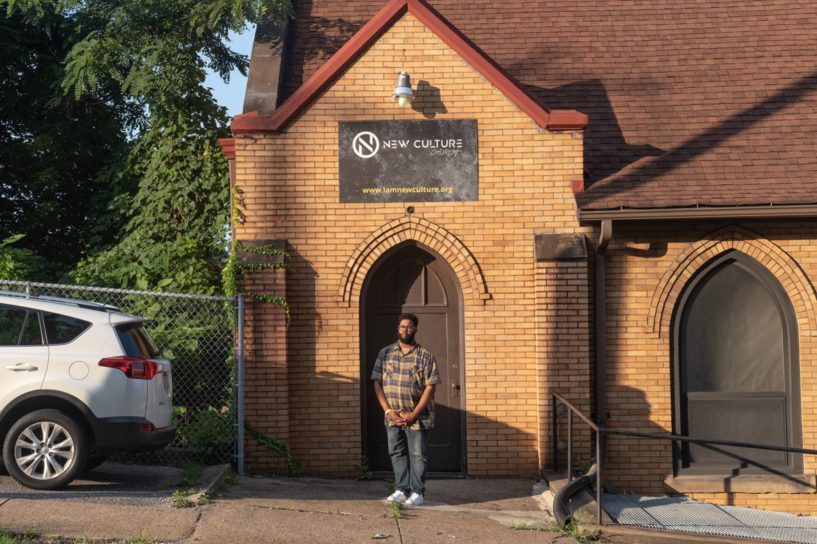 Rev. Justin Louis Murrell stands in the arched doorway of New Culture Church. A sign overhead advertises the church's name.