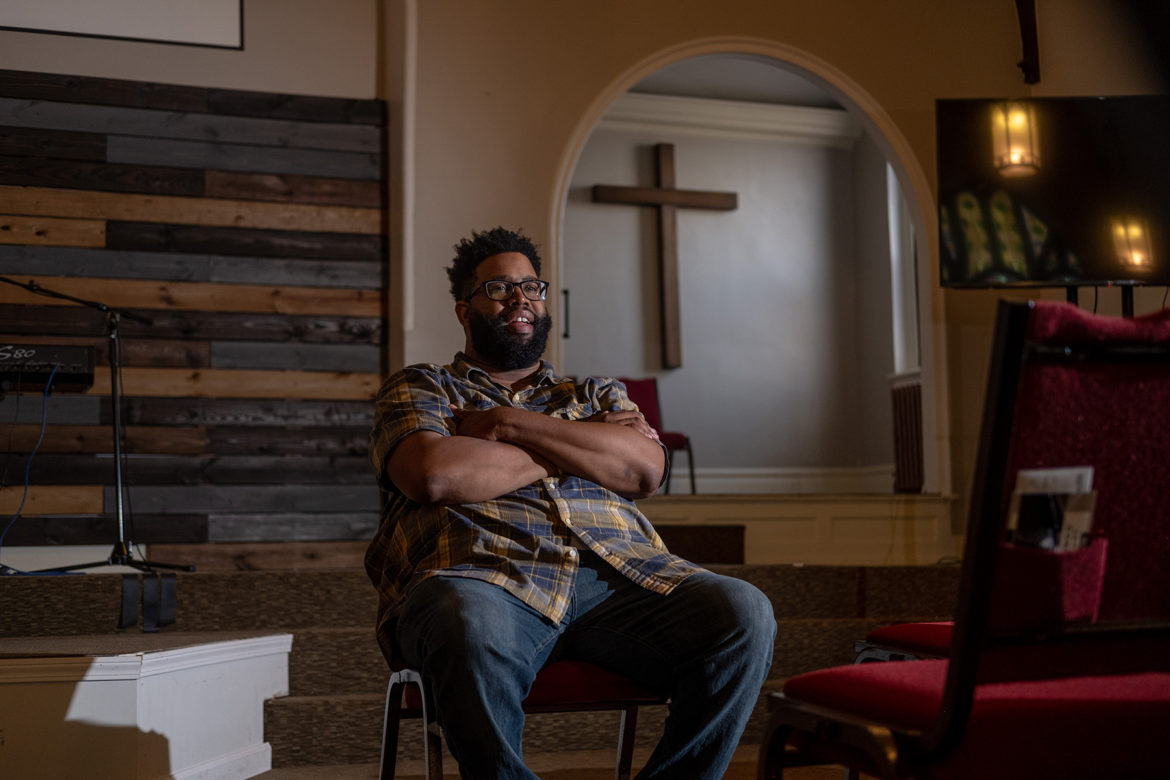 Rev. Justin Louis Murrell sits in the worship space of New Culture Church. A cross is visible behind him.