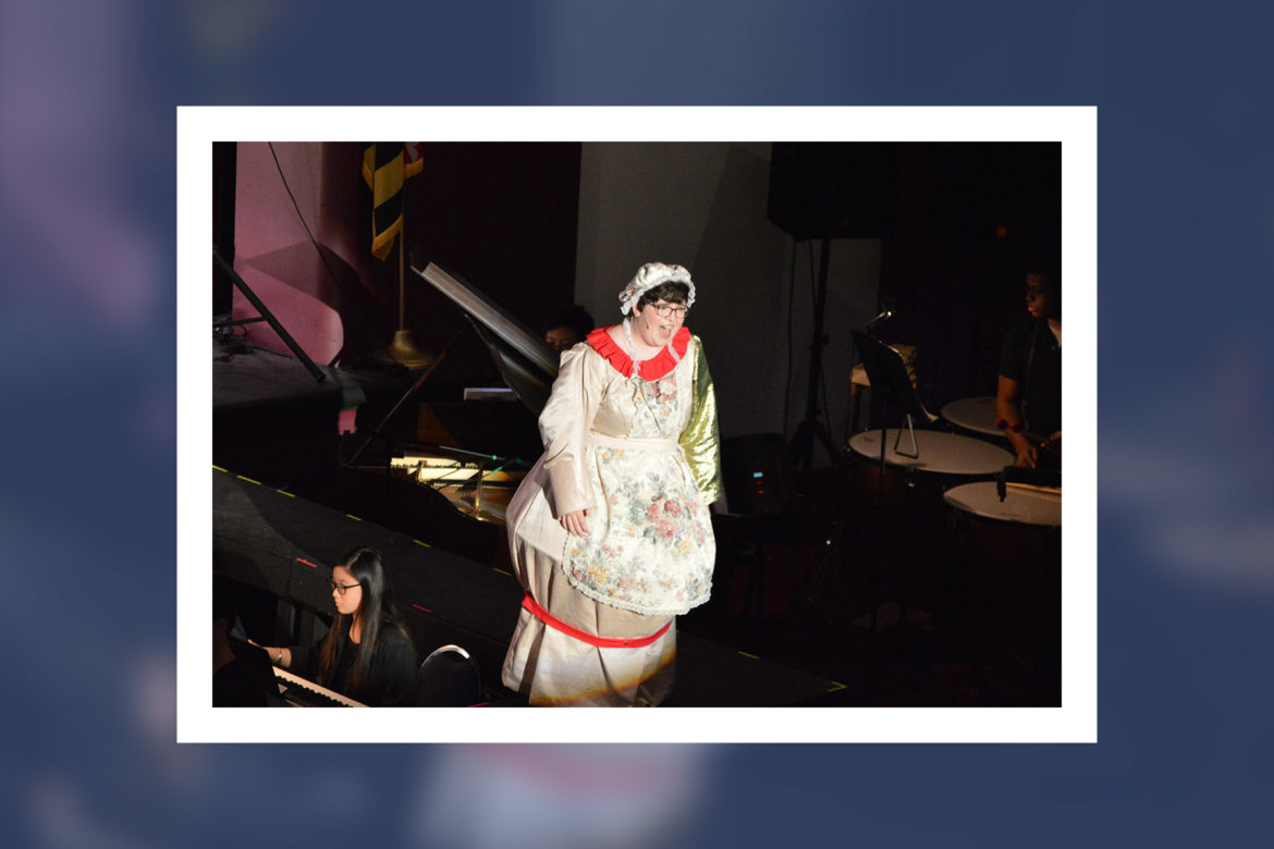 Anna Skeels performs on a stage wearing a dress, bonnet and floral apron.