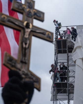 Right wing extremists and Trump supporters shout from scaffolding on the United States Capitol building encouraging others to join them in attacking the Capitol on January 6, 2021.