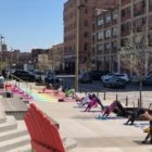People practice yoga positions on a sidewalk area outside on a sunny day.