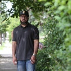 Julius Boatwright wears a Black polo, blue jeans and a black hat. He is standing on the sidewalk next to some bushes.