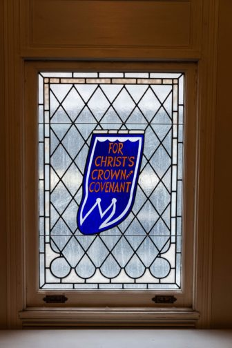 """A stained glass window in Rev. Barry York's office reads """"Christ's crown and covenant."""""""