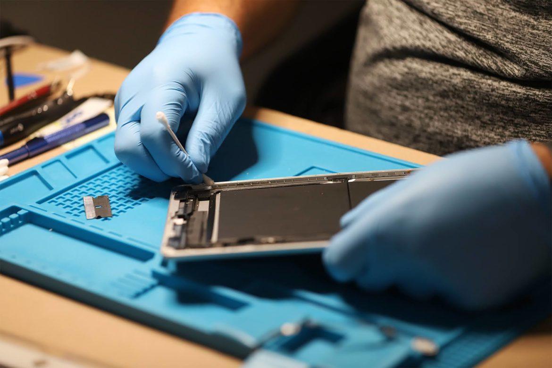 Josh Turkovich, owner of Mon Valley Phone Repair in Monessen, Pa., repairs an iPad in his shop. (Photo by Ryan Loew/PublicSource)