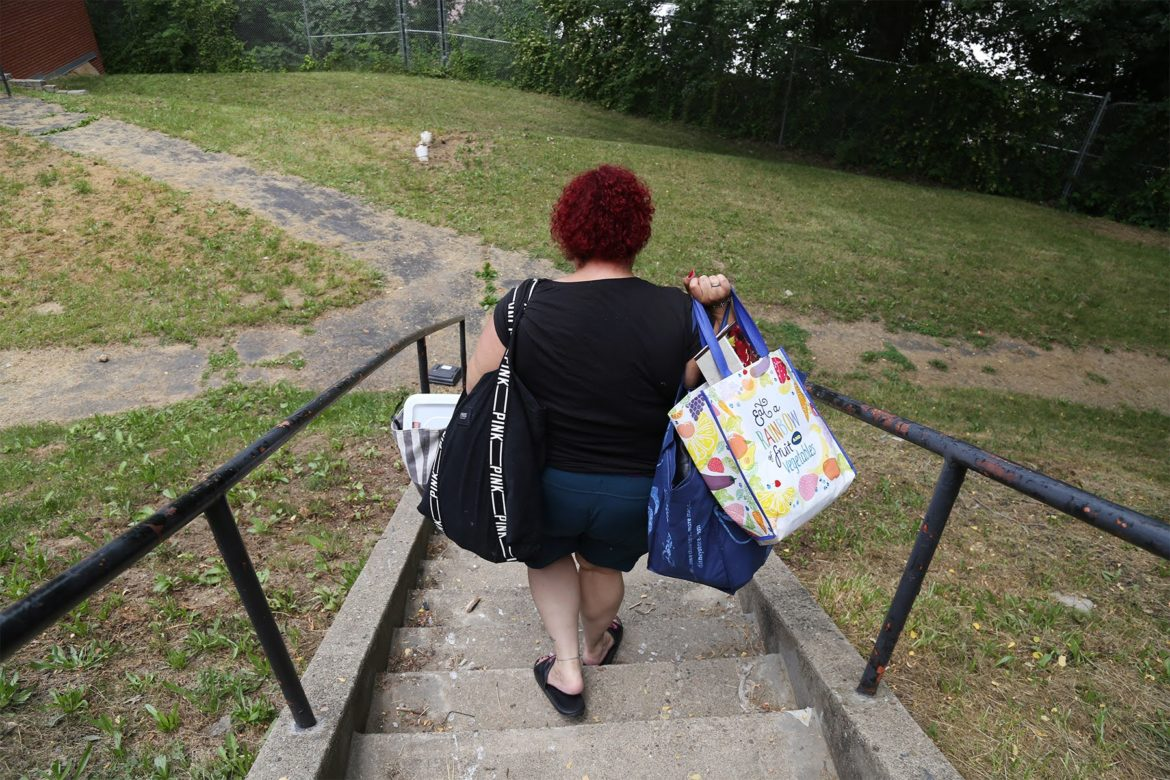 Beatrice Román carries belongings to a new apartment in Hi View Gardens on June 10, 2021. (Photo by Ryan Loew/PublicSource)