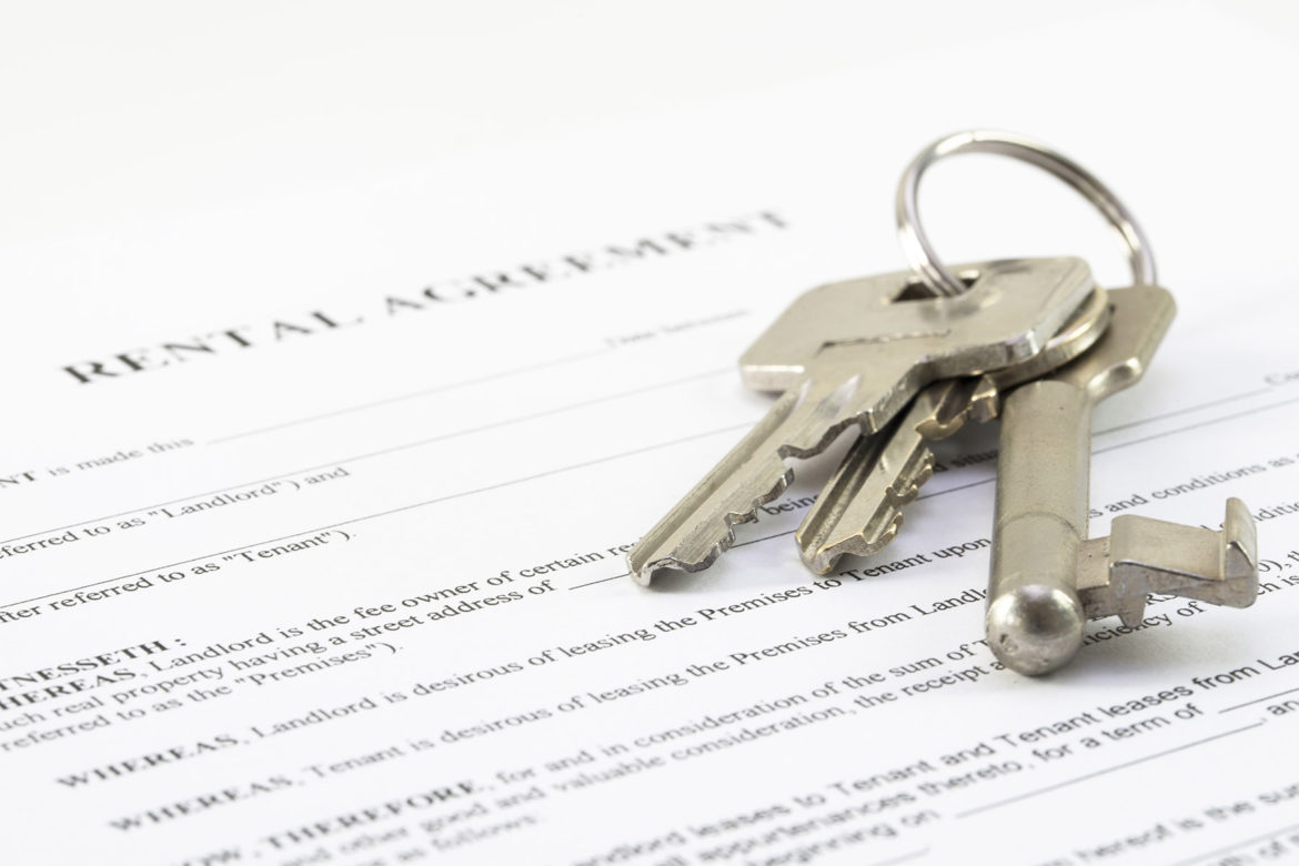 Three silver keys bound on a ring laid across a rental agreement document