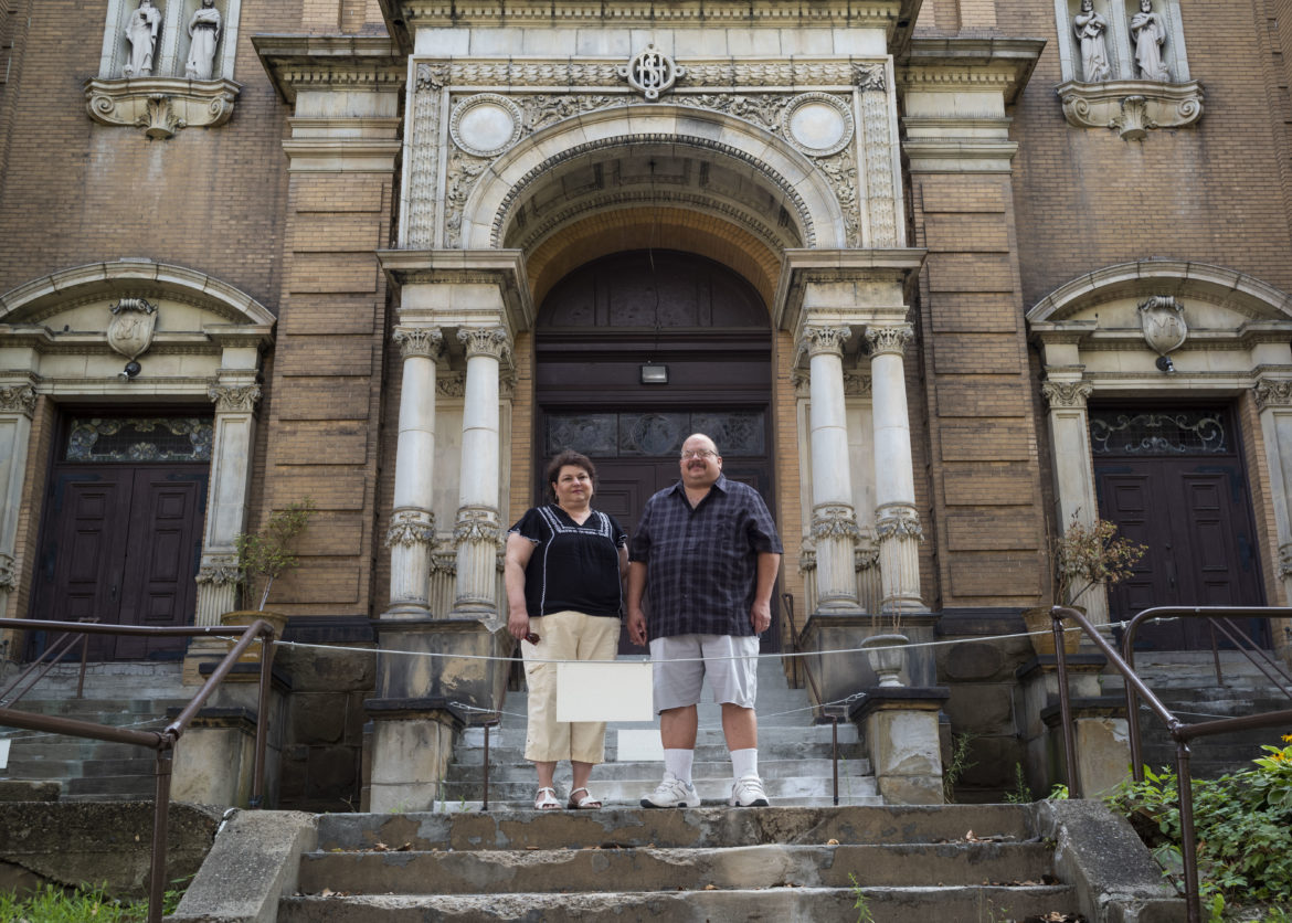 Rose and John Velgich-Figlar stand behind the ropes blocking off the front steps of St. Stephen's Catholic Church in Hazelwood. The church has been closed since September 2020.