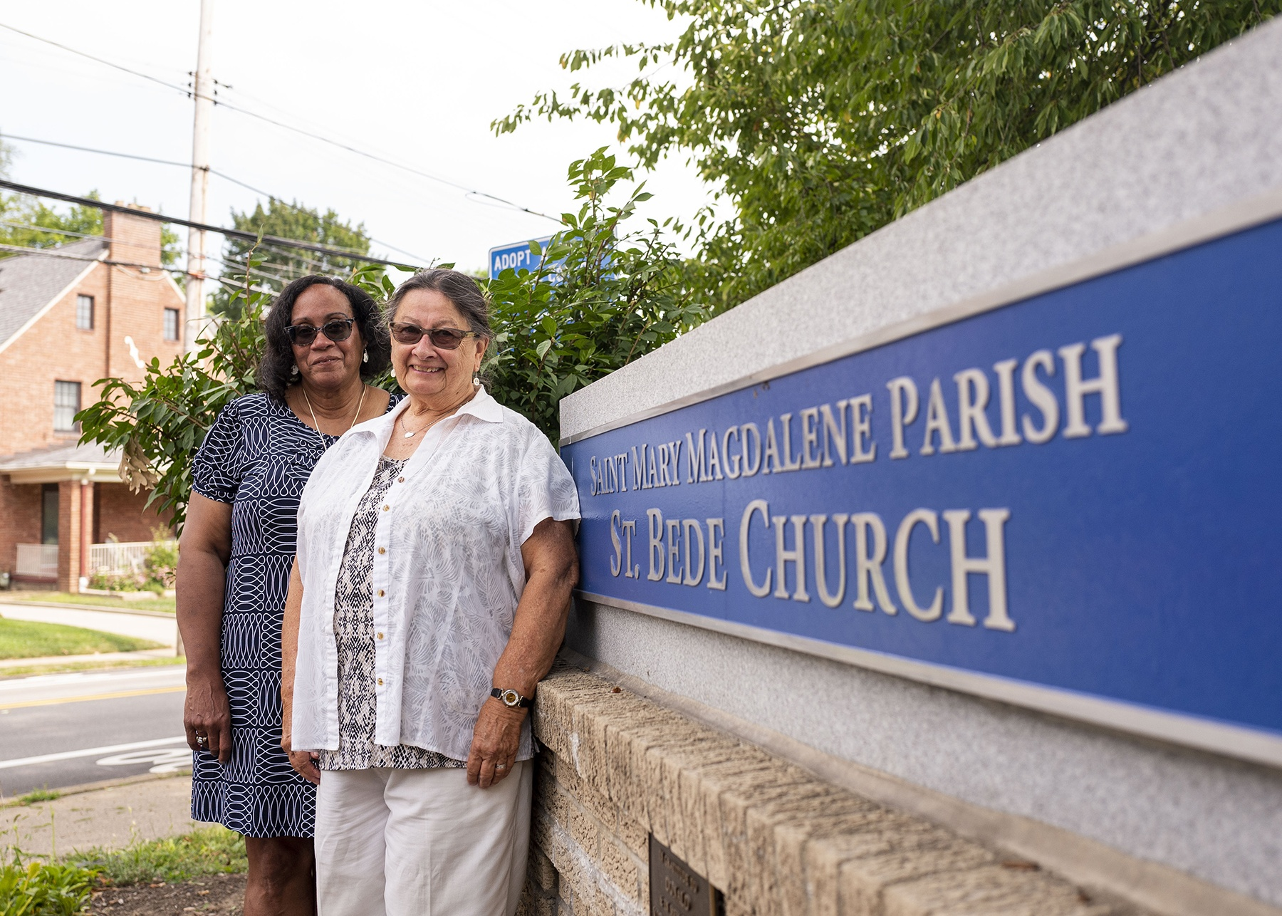 """Joyce Rothermel, right, and Sharon Currie, left, members of St. Mary Magdalene Parish, stand by a large outdoor sign that reads """"St. Mary Magdalene Parish, St. Bede Church."""""""