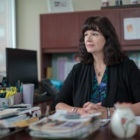 Nicole Molinaro, president and CEO of Women's Center and Shelter of Greater Pittsburgh, sits at a desk.