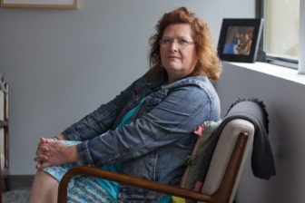 Grace Coleman sits in a chair looking into the camera for a photograph.